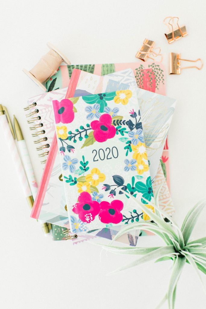 On voit un agenda 2020 avec des fleurs, des cahiers, deux stylos blancs et dorées, des pinces dorées et  une plante grasse.